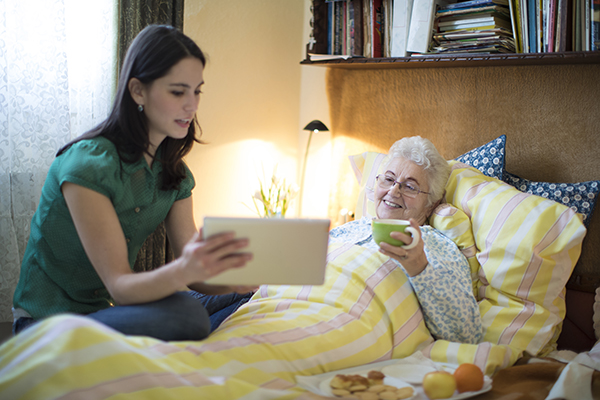 caregiver showing tablet to senior woman