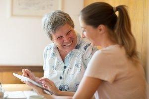 caregiver showing digital tablet to senior woman
